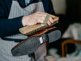 Old shoemaker is polishing a shoe